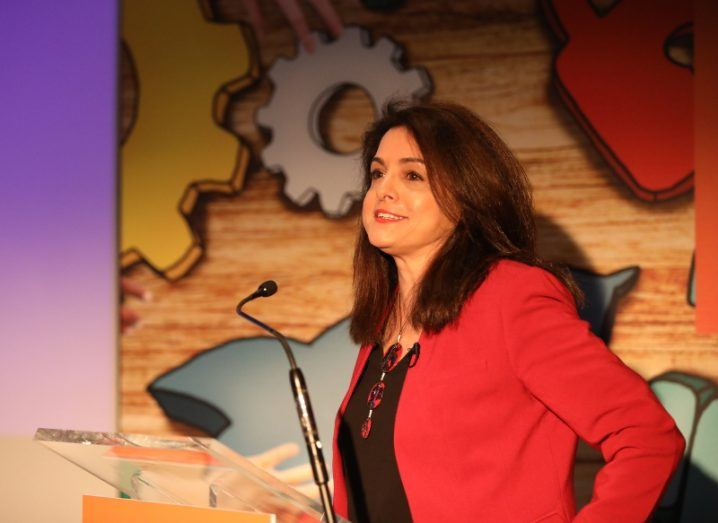 A dark-haired woman in a red blazer stands at a podium in front of a colourful backdrop.