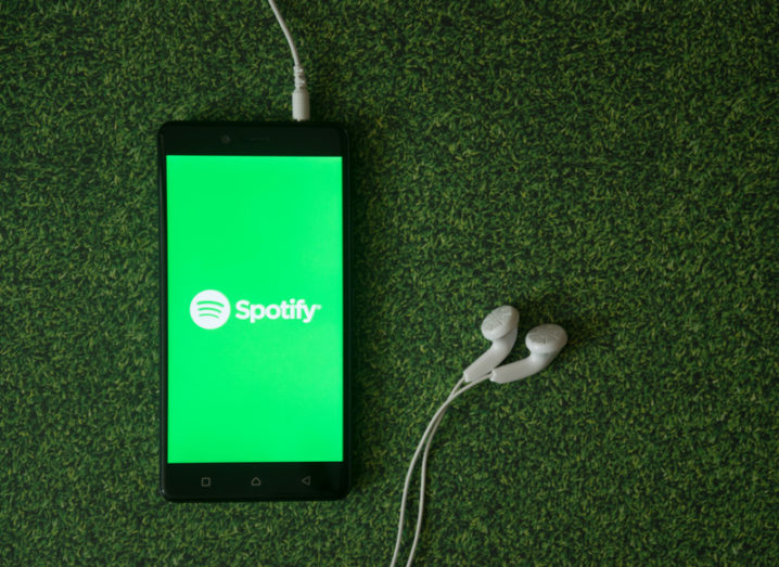 Spotify on a mobile device with headphones.