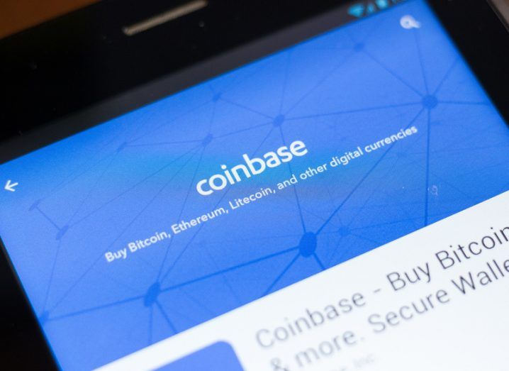 A view of the blue screen of the Coinbase app on a smartphone sitting on a mahogany table.