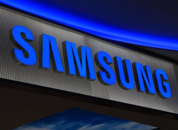The Samsung logo on a building, lit up in royal blue.