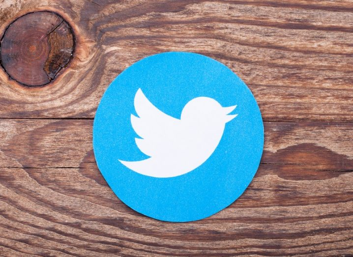 Twitter bird logo cut into a circle, resting on a dark wood surface.