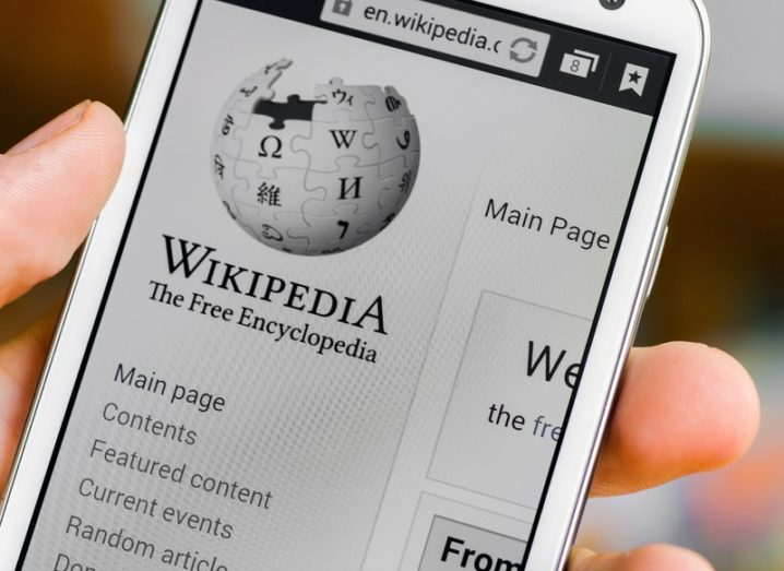 Hand holding a smartphone displaying the Wikipedia homepage.