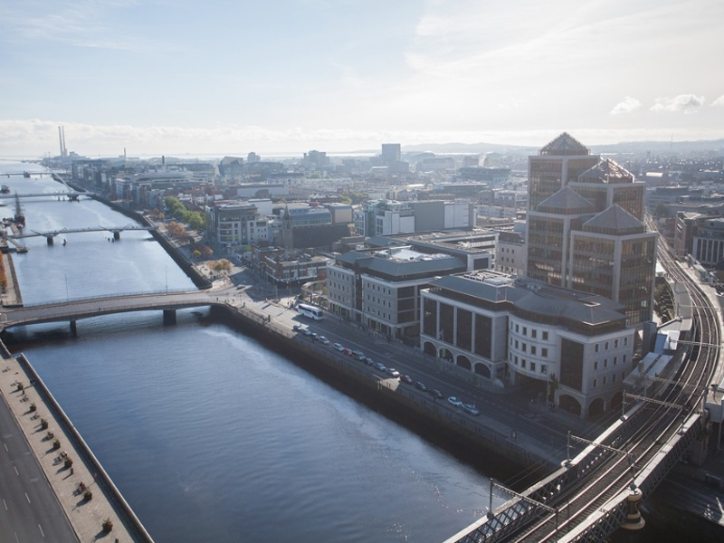 Aerial view of Dublin's Liffey with a train track running across bridge.