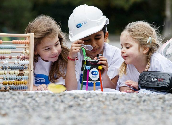 Three young girls, one in a builder's helmet, analysing a piece of scientific kit.
