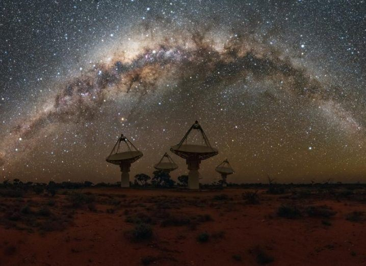 The dish antennas of the radio telescope against a stunning star-filled night sky.