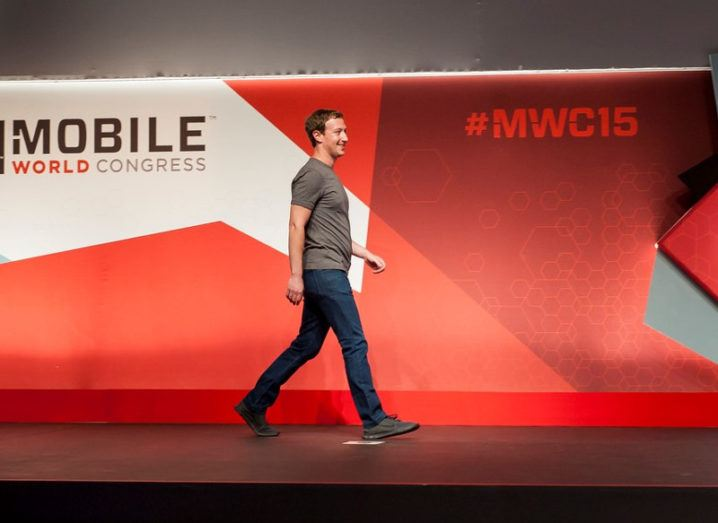 young man in grey t-shirt strides across stage at Mobile World Congress.