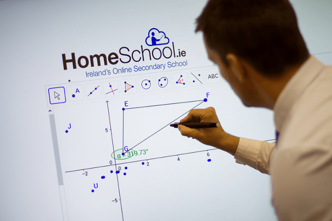 Man writing a maths lesson on a whiteboard.