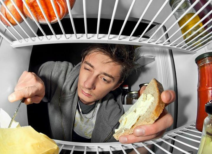 Tired man at night sticking his head in the fridge while spreading butter on a piece of bread.