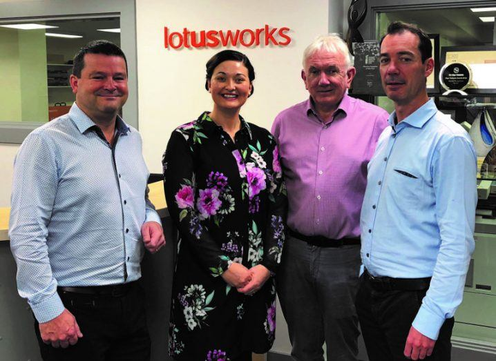 Three men and a woman stand in front of a LotusWorks sign.