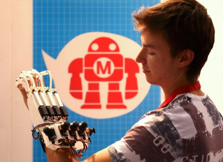 Teenager wearing a 3D-pritned robotic arm in front of the Maker Faire logo.