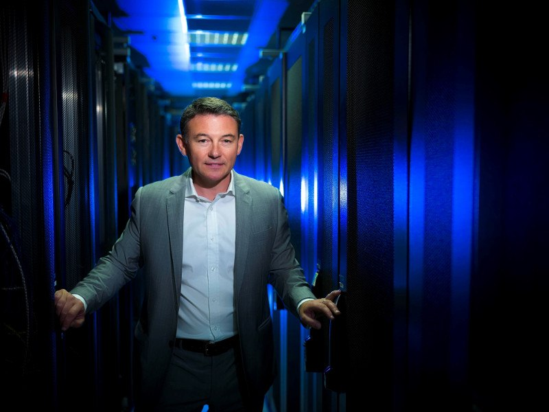 Man standing in suit in data centre.