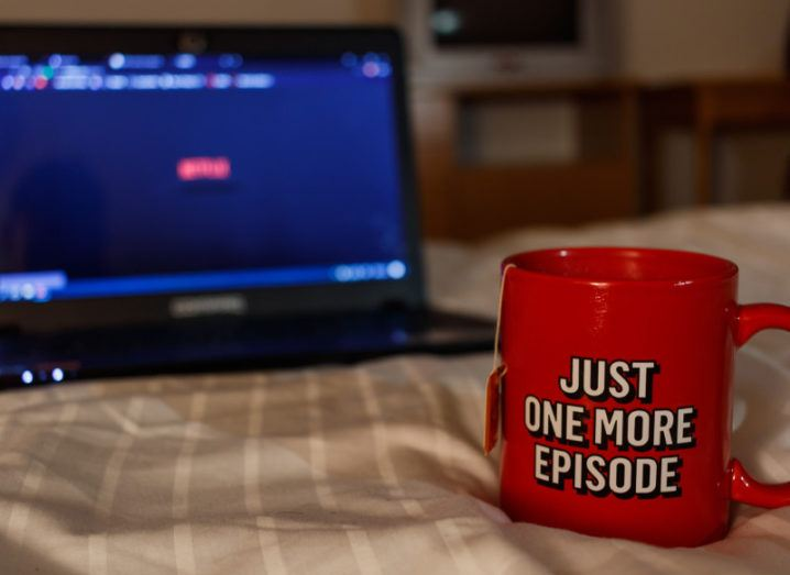 Picture of a mug of tea saying just one more episode in front of a laptop running Netflix.