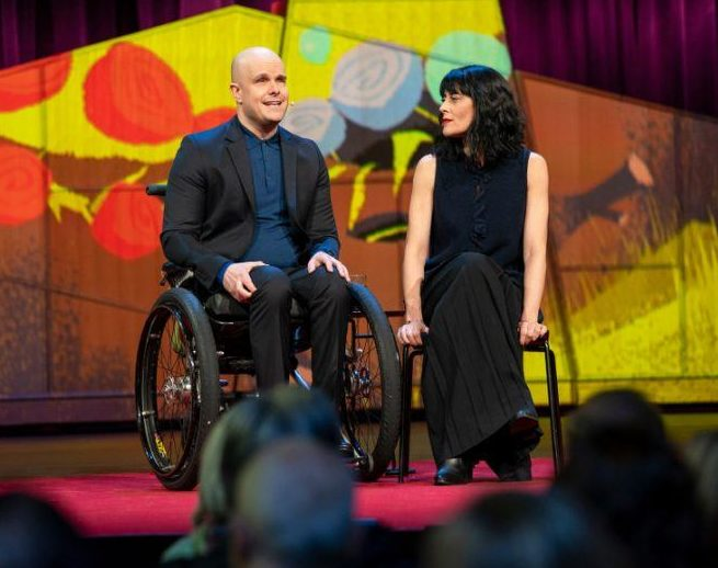 From left: Mark Pollock sitting in a wheelchair, Simone George sitting in a chair on stage.