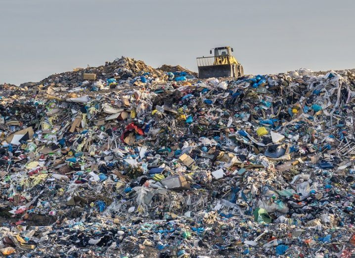 Bulldozer sitting on top of an enormous pile of plastic, taking up almost the entire image.