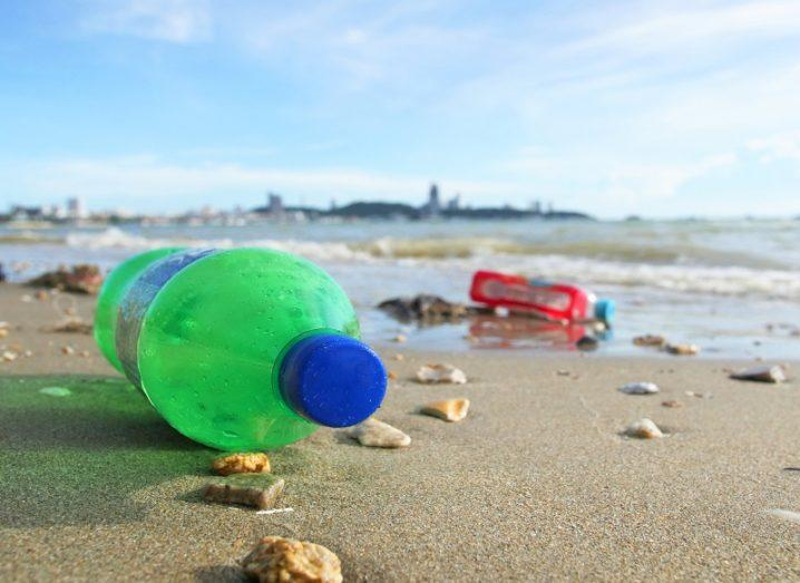 Close-up of a green plastic bottle washed up on to the beach.