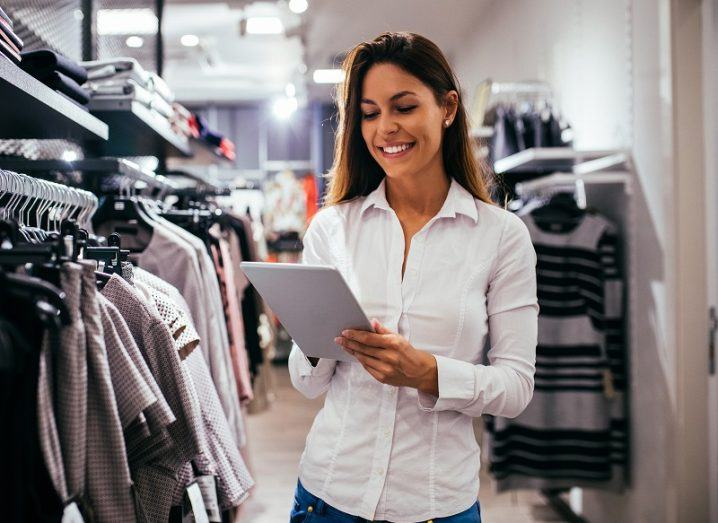 Smiling woman in a white shirt holding a tablet in a clothing store.