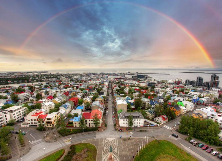 A view of Iceland's capital city Reykjavik looking out to sea with a rainbow crossing the harbour.