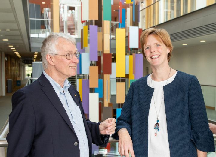 In front of a colourful hanging sculpture, a grey-haired man smiles at a woman with short hair who is looking at the camera.