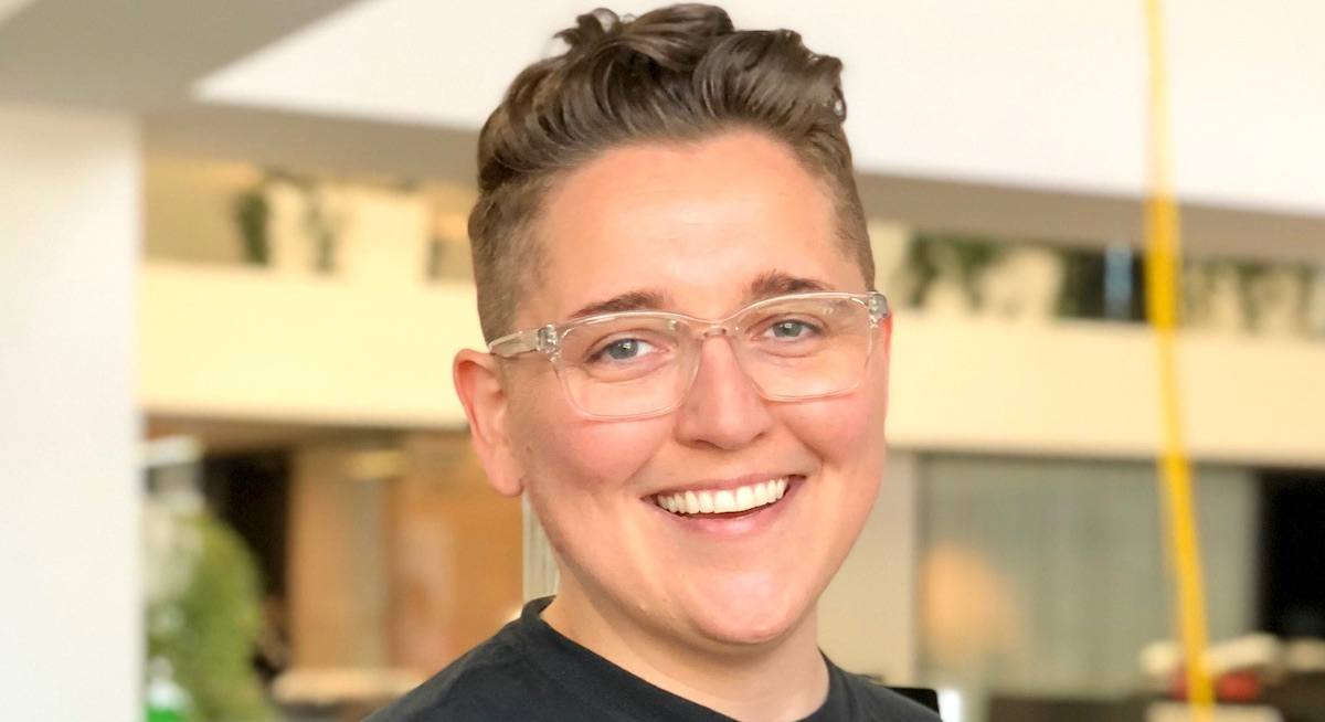 A headshot of a smiling young woman with short hair and glasses. She works at Spotify.