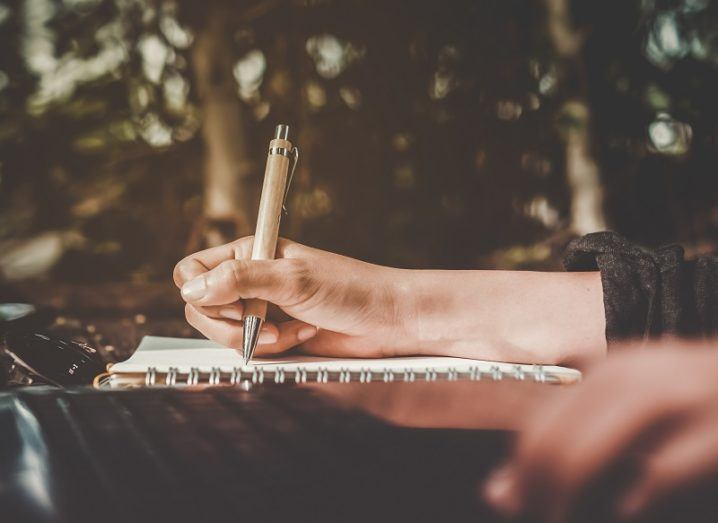 Sideways shot of a person's hand holding a pen over a copybook while also using a laptop.