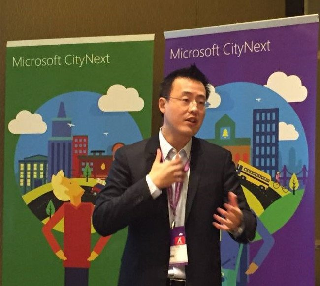 Dark-haired man wearing suit and glasses speaking in front of green and purple MIcrosoft posters.