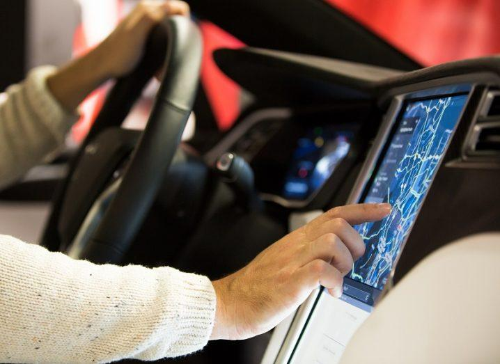 Driver in a Tesla car reaching to the touchcreen control panel with one hand on the steering wheel.