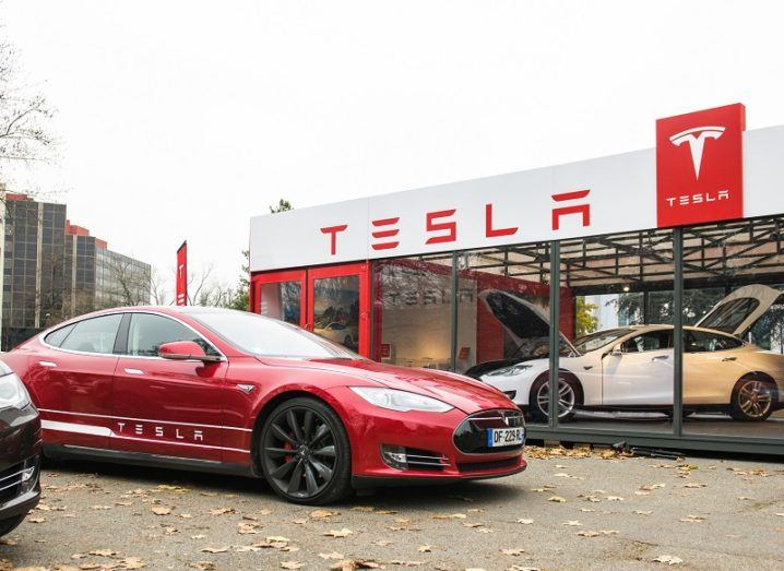A red Tesla Model S in front of a Tesla dealership in autumn.