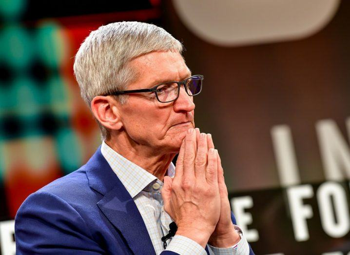 Apple CEO Tim Cook wearing a blue suit, holding his hands together under his chin.