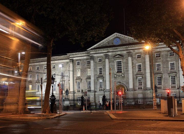 Front of Trinity College Dublin lit up at night with bus appearing into view.