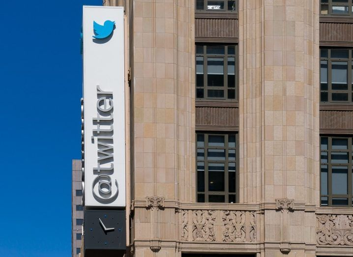 A Twitter sign showing its logo on the side of a tall building.