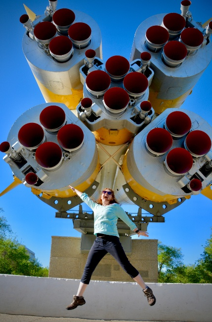 A women joyously leaps in the air with arms and legs outstretched in front of a bottom-up view of rocket thrusters.