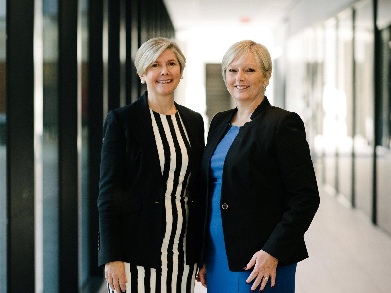 Two women with blonde hair and black jackets stand in a corridor.