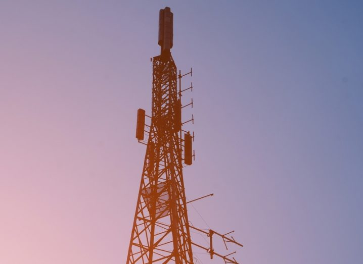A mobile signal mast with a glowing pink sky behind it.