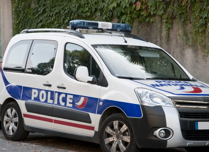 A French police car parked on the street with an ivy-covered wall behind it.