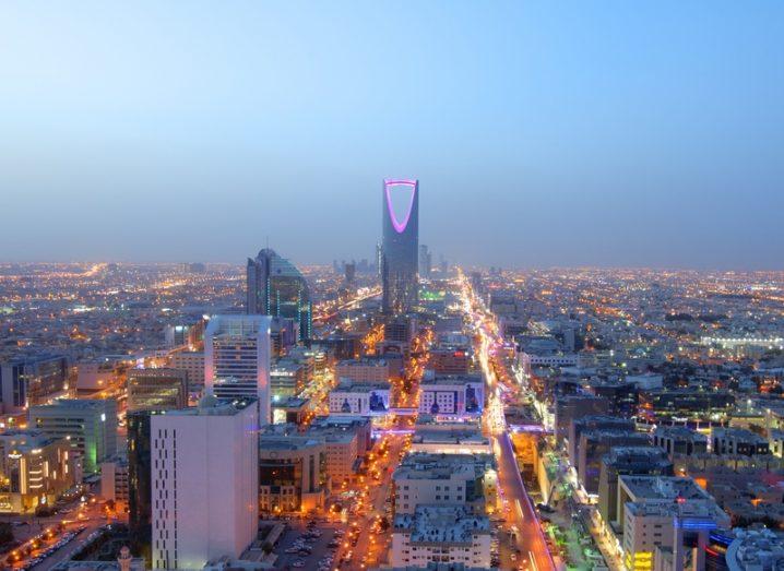 Riyadh city skyline at night, with bright buildings lit up.