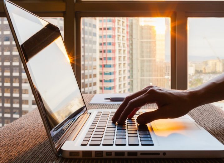 A hand typing on a MacBook with skyscrapers outside a large window.
