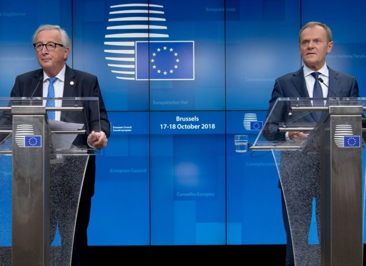 From left: Jean-Claude Juncker and Donald Tusk on stage at separate podiums with EU imagery in the background.