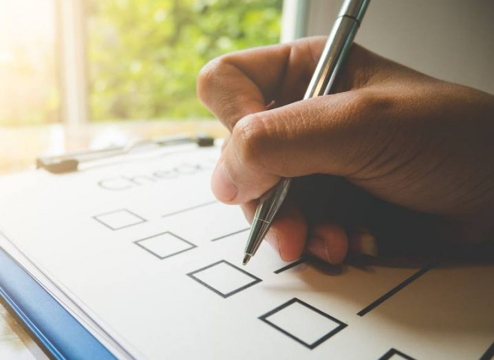 Close-up of hand holding a pen, ticking boxes on a checklist.