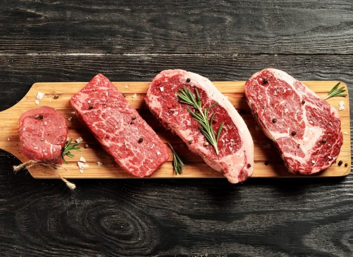 Fresh raw beef steaks on a wooden platter, resting on a black surface.