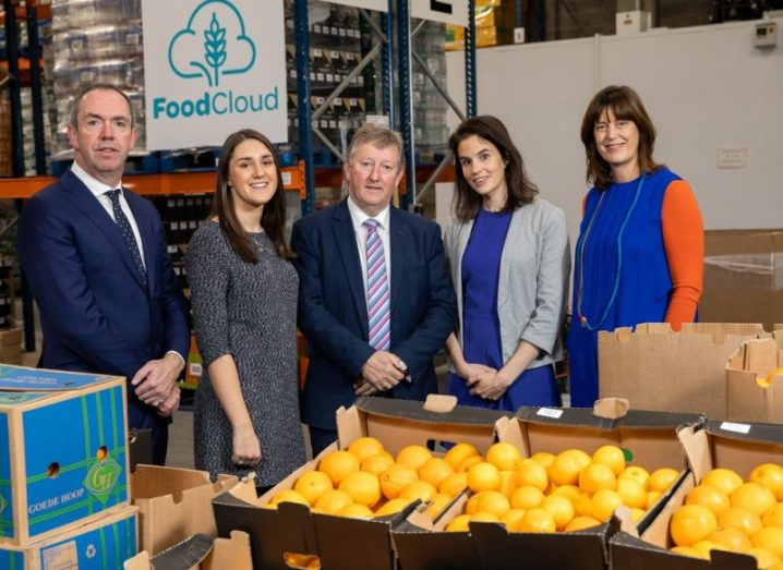 group of five people standing in a food distribution hub in front of boxes of oranges, with foodcloud logo in the background.