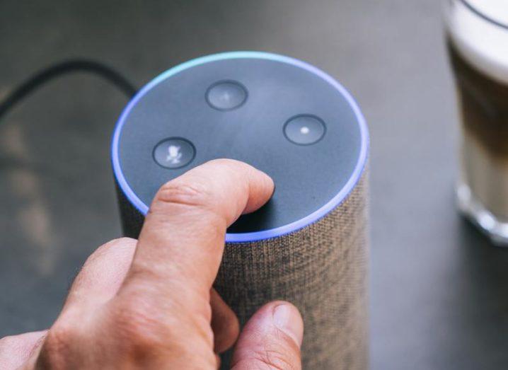Male hand pressing button on Amazon Echo smart speaker.