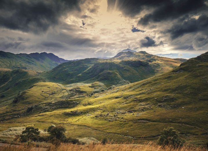 The hills of Snowdonia, Wales, with a dramatic cloudy sky in the background.