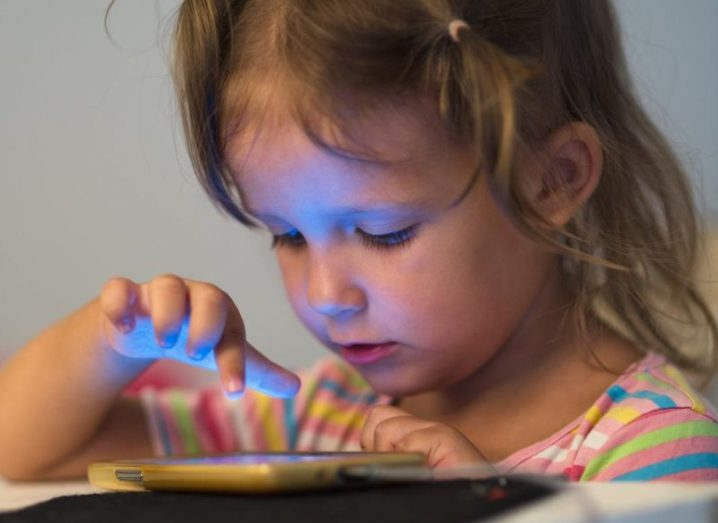 A little girl playing with a smartphone. The blue light is shining on her face.