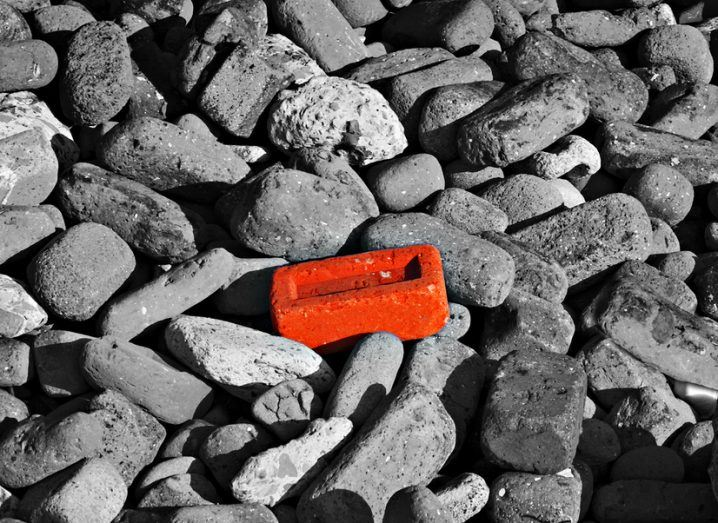 Single red brick among lots of monochrome pebbles.