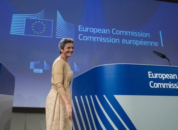 Margarethe Vestager walking towards a podium at an EC press conference.