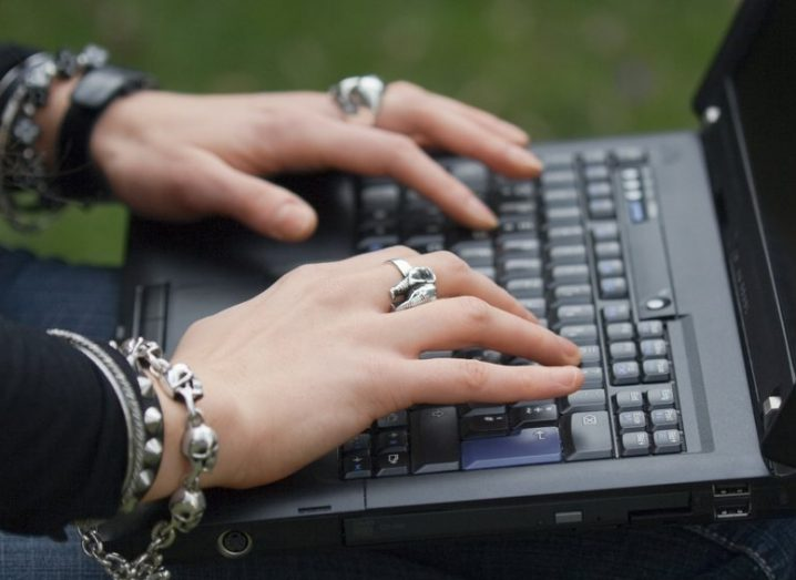 Hands typing on a laptop, wearing lots of rings and bracelets.
