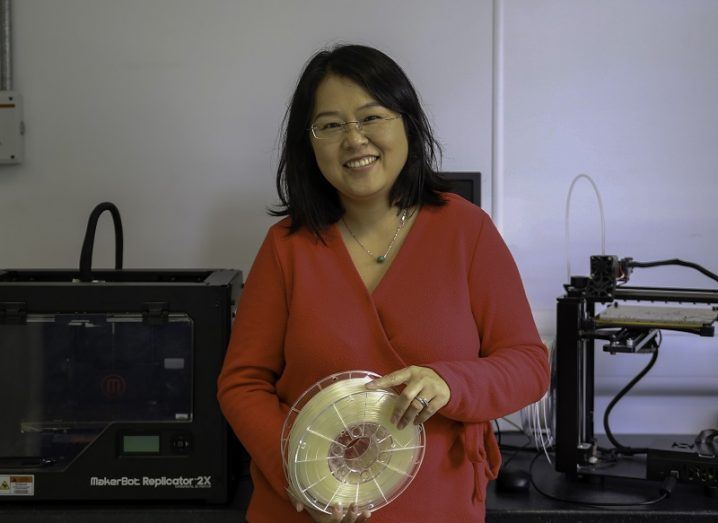 Dr Yuanyuan Chen holding a spool of 3D printing filament with 3D printers in the background.