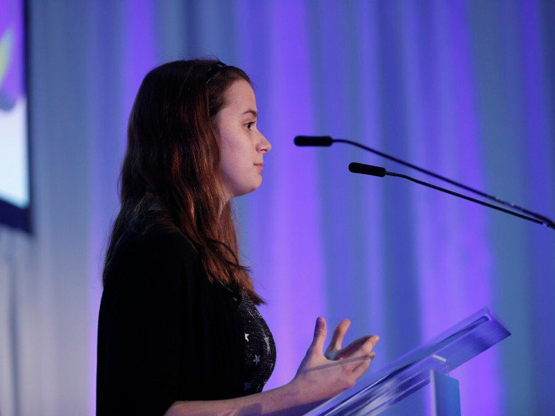 side view of young girl with long brown hair speaking on stage in front of microphone and purple backdrop.