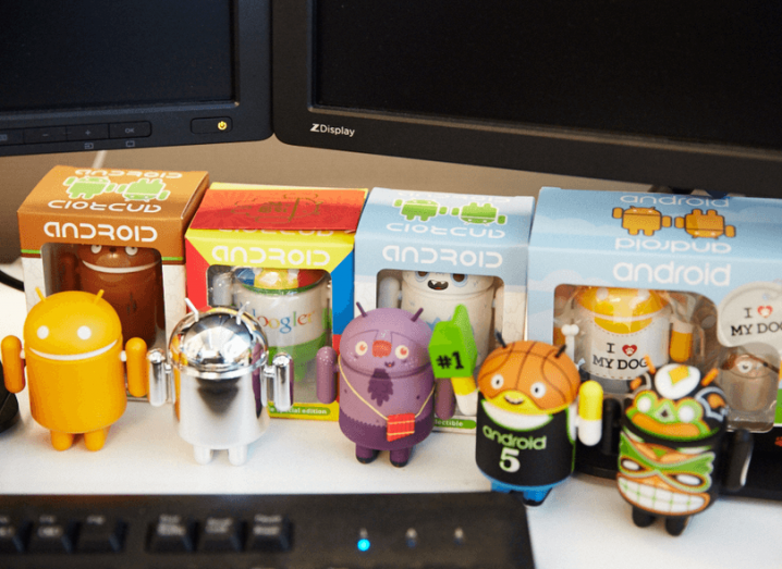 A group of plastic Android mascot figurines standing at a computer desktop.