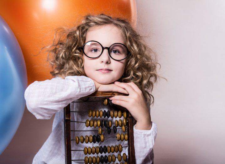 Girl with curly hair and glasses leans on an abacus.